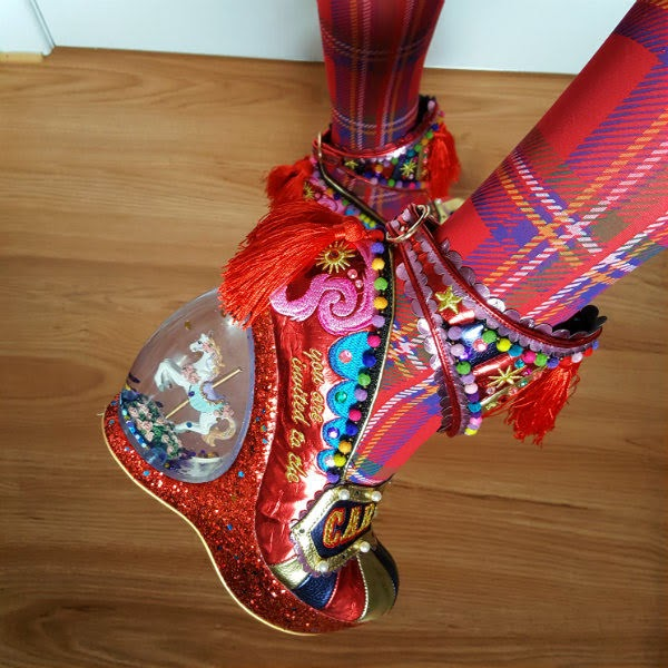 close up of transparent glitter globe heel of shoe with circus carousel horse inside