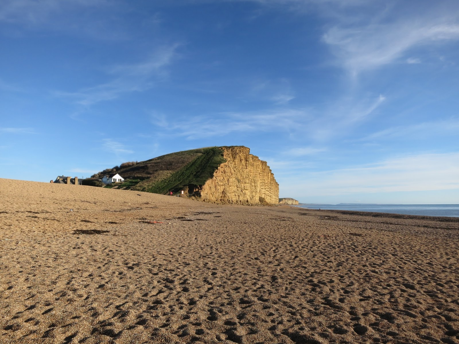 West Bay end of cliff with pebbles in foreground and sea beside.