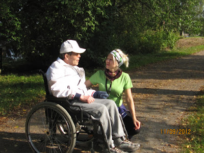 Vihreäpaitainen nainen on polvillaan maassa ja juttelee rullatuolissa olevalle vanhusmiehelle.
