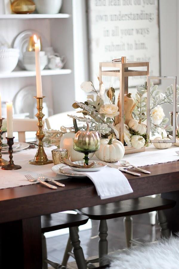 Mesa decorada con calabazas, candelabros y detalles en dorado