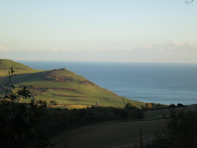 Conical hill, ploughed field and sea taken from the path up to Golden Cap, Dorset
