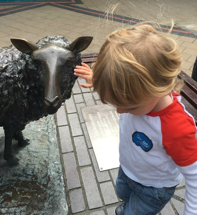 toddler-with-sheep-statue-in-Abergavenny