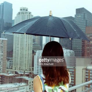 Γυναίκα όρθια σε μπαλκόνι κρατώντας ομπρέλα. Ακολουθεί το κείμενο: Βρέχει... Μία κυρία εξέχει στη βροχή μόνη πάνω σ' ένα ακυβέρνητο μπαλκόνι. Κι είναι η βροχή σαν οίκτος κι είναι η κυρία αυτή σαν ράγισμα στη γυάλινη βροχή. Το βλέμμα της βαδίζει στη βροχή, βαριές πατημασιές καημού τον βρόχινό του δρόμο γεμίζοντας. Κοιτάζει... Κι όλο αλλάζει στάση, σαν κάτι πιο μεγάλο της, ένα ανυπέρβλητο, να 'χει σταθεί μπροστά σ' εκείνο που κοιτάζει. Γέρνει λοξά το σώμα παίρνει την κλίση της βροχής ―χοντρή σταγόνα μοιάζει― όμως το ανυπέρβλητο μπροστά της πάντα. Κι είναι η βροχή σαν τύψη. Κοιτάζει... Ρίχνει τα χέρια έξω απ' τα κάγκελα τα δίνει στη βροχή πιάνει σταγόνες φαίνεται καθαρά η ανάγκη για πράγματα χειροπιαστά. Κοιτάζει... Και, ξαφνικά, σαν κάποιος να της έγνεψε «όχι», κάνει να πάει μέσα. Πού μέσα ― μετέωρη ως εξείχε στη βροχή και μόνη πάνω σ' ένα ακυβέρνητο μπαλκόνι.