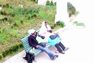 Dos emigrantes negras, tocadas con pañuelos, sentadas en un banco