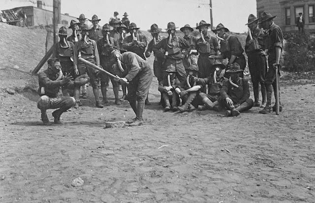 Soldiers playing baseball while wearing gas masks. Original caption: It is not troubling these soldiers any to play ball while wearing their gas masks. Gas Defense Plant, Long Island, New York.