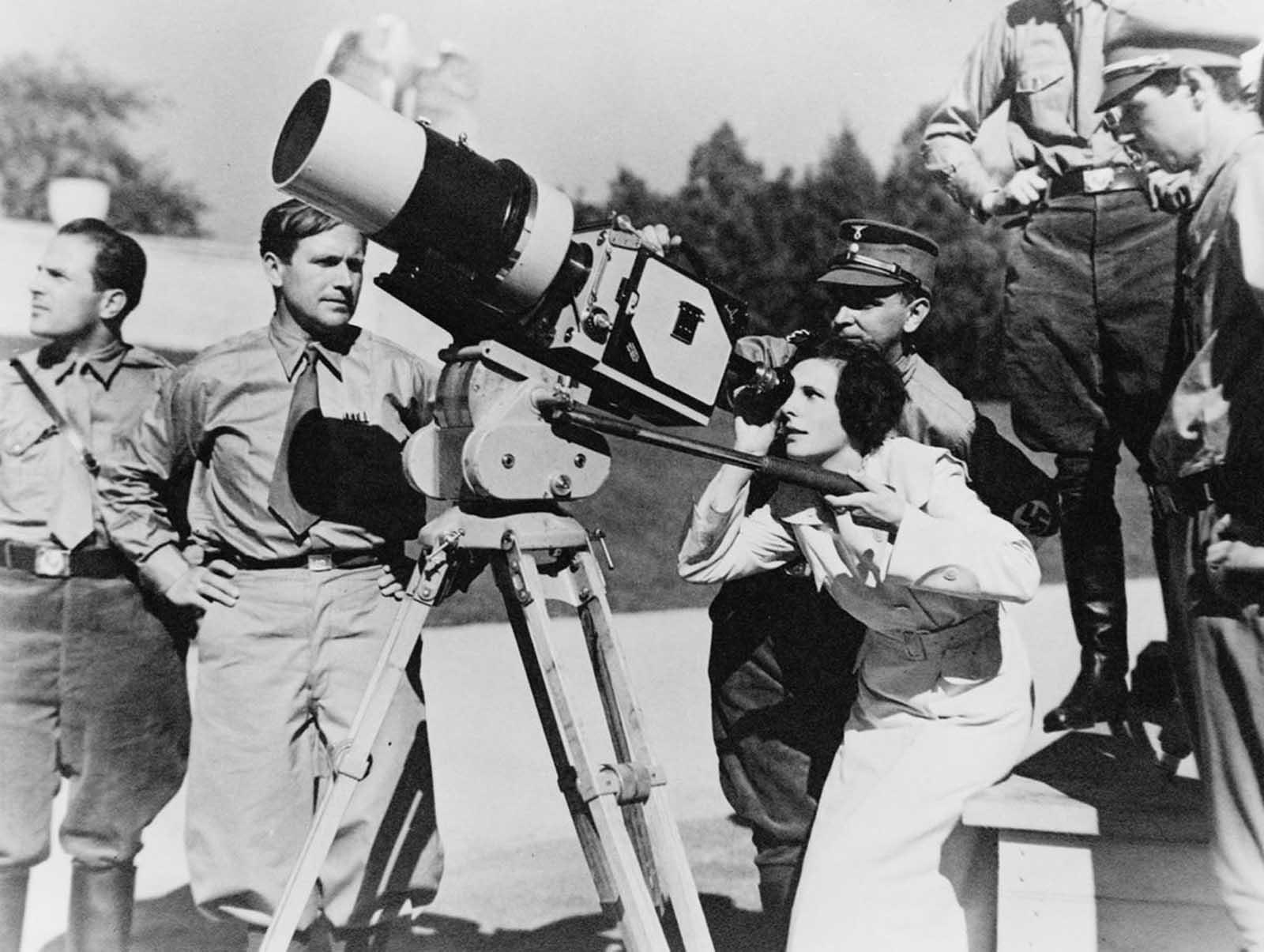 La cineasta Leni Riefenstahl mira a través de la lente de una gran cámara antes de filmar el Rally de Nuremberg de 1934 en Alemania. El metraje se compondría en la película de 1935.
