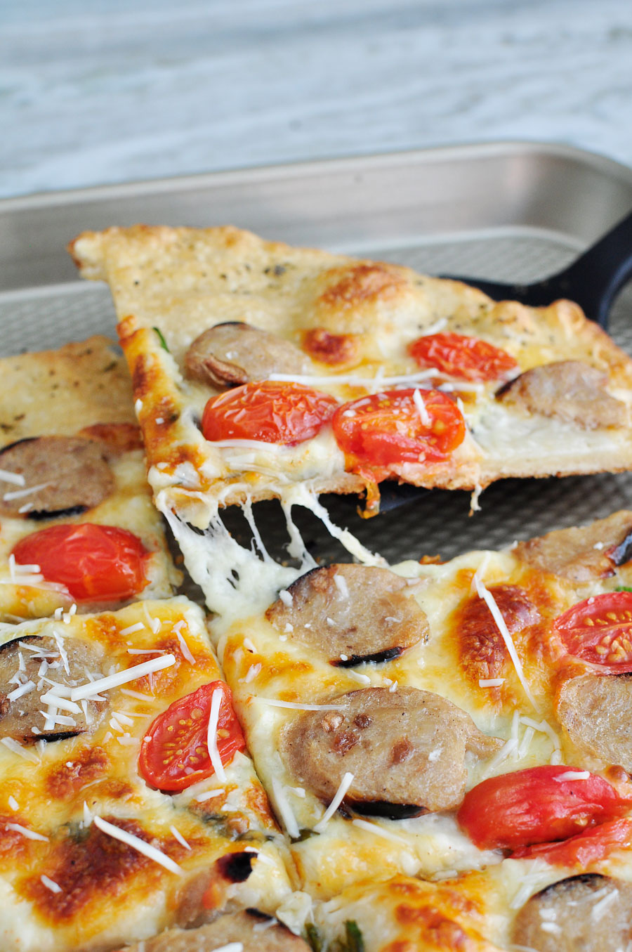 Rustic flatbread chicken sausage pizza recipe with spinach, alfredo, tomatoes and mozzarella. Weight Watchers friendly!