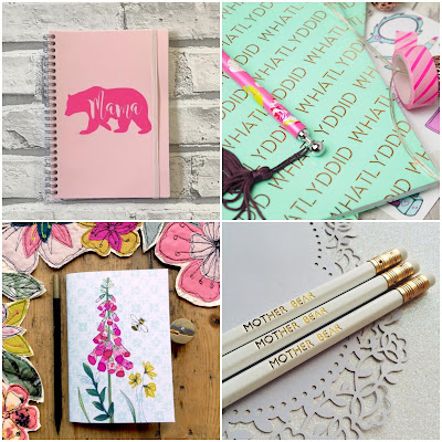 1: a pink notebook with a hot pink bear silhouette on it. The bear has 'mama' written in it. 2: a notebook wrapped in mint green paper printed with 'whatlyddid' in gold foil. 3: a notebook with a pink foxglove, yellow flowers, and a bee on the cover. 4: white pencils reading 'mother bear' in gold foil.