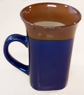 A large square coffee mug with brown rim and navy blue body.