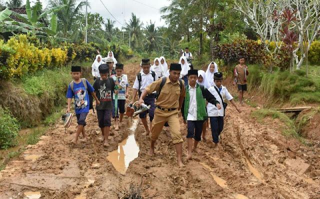 Guru Madrasah dan Murid-muridnya Melalui Jalan Rusak