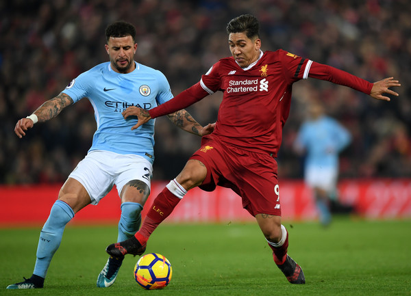 Kyle Walker of Manchester City and Roberto Firmino of Liverpool battles for possesion during the Premier League match between Liverpool and Manchester City at Anfield on January 14, 2018 in Liverpool, England.