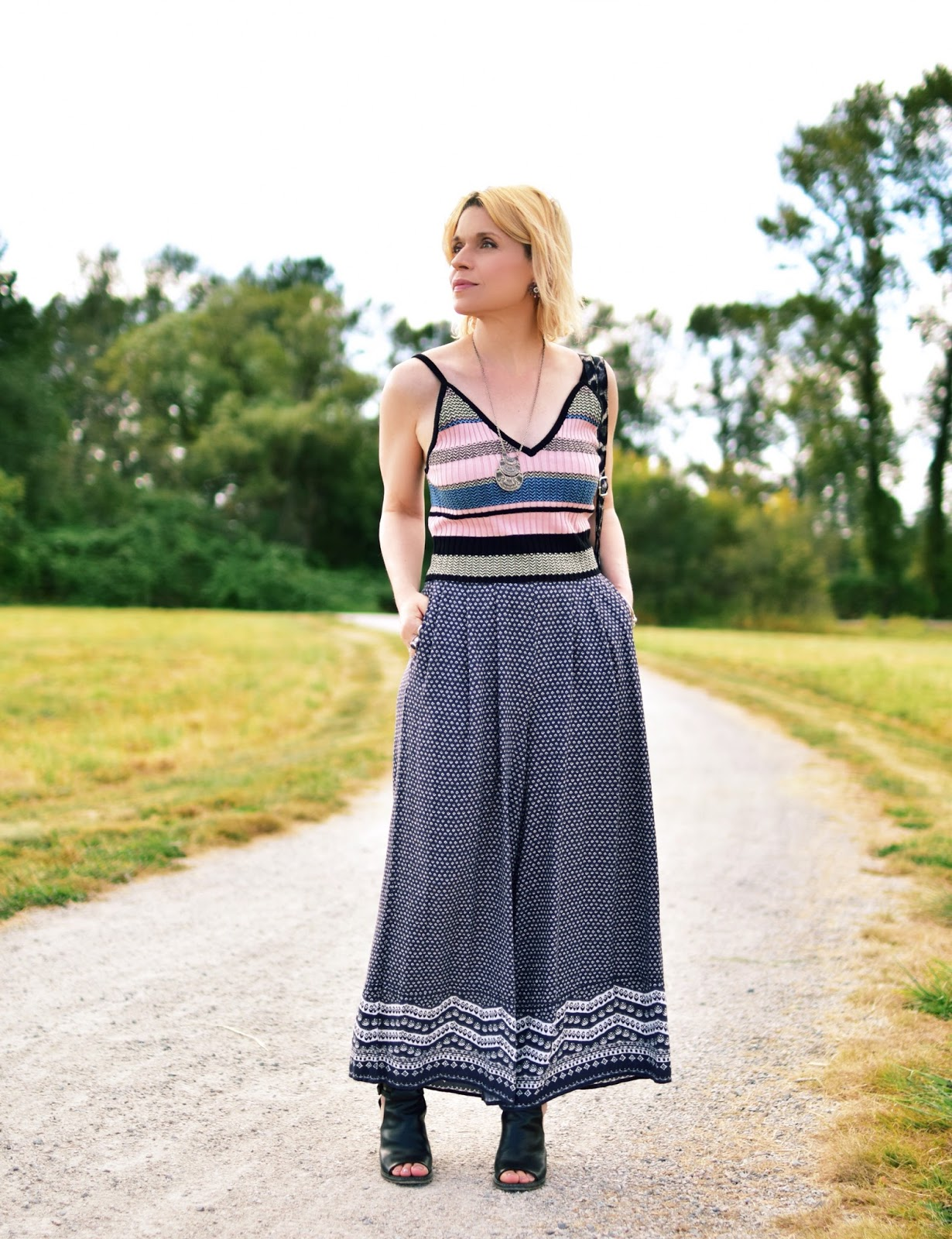 Monika Faulkner styles patterned palazzo pants with a striped tank top and cut-out booties