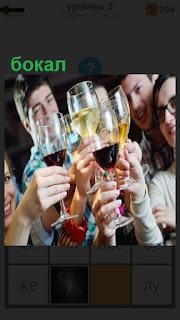 Несколько молодых людей держат в руках бокалы с вином