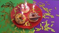 Tres donuts decorados de diferente forma con velas de cumpleaños.