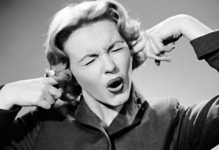 Imagen en blanco y negro de una mujer de los 80s tapándose los oídos con los dedos y cerrando los ojos.