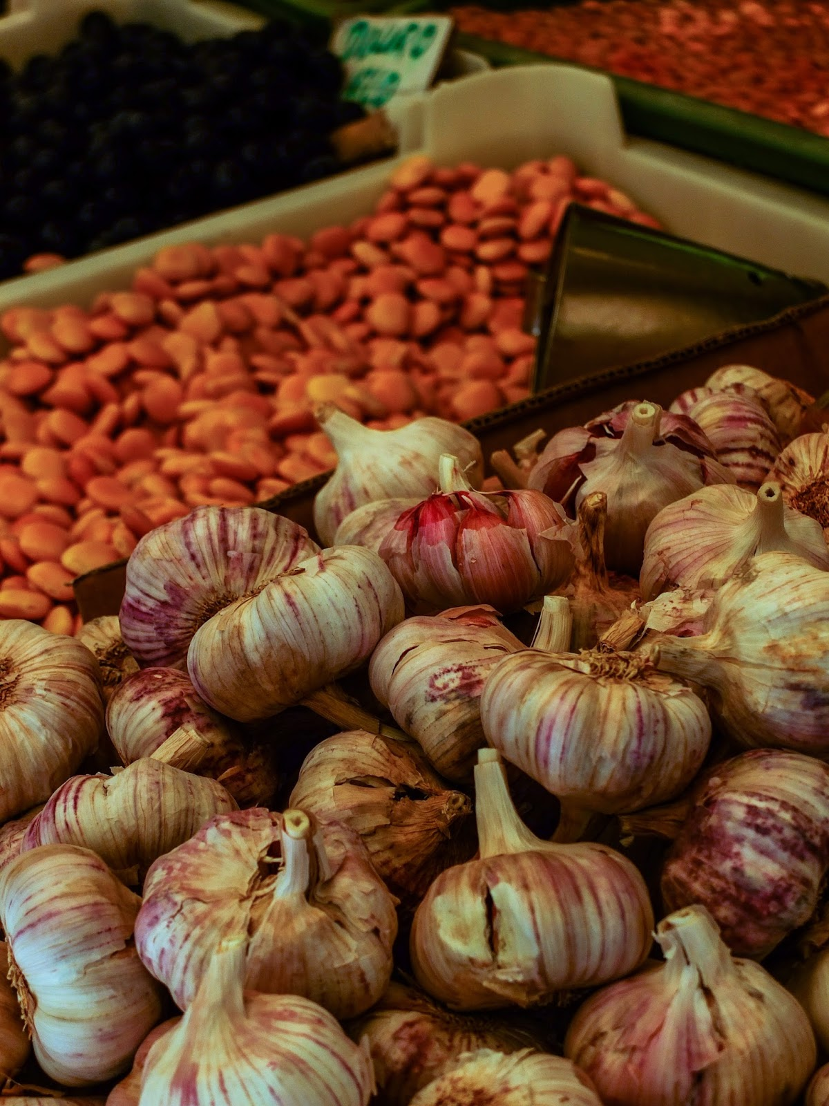 Bulbs of garlic and beans at a market in Porto, Portugal.