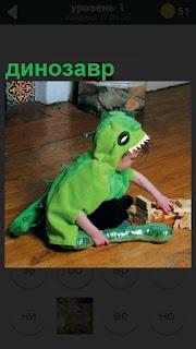 На полу играет ребенок в костюме динозавр зеленого цвета