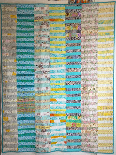 Improvisationally pieced Chinese Coin quilt in turquoise, yellow, and white.