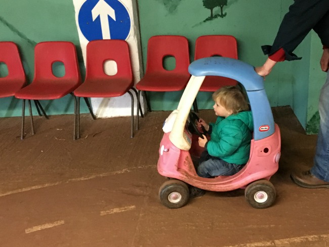 a toddler sat in a pedal car with roof