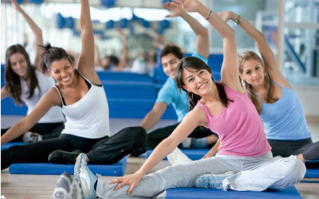 hombres y mujeres practicando deporte en gimnasio
