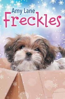 Cover of Freckles, featuring a brown and white Shih Tzu puppy standing in a cardboard box. Her ears and perked and her tail is up. Stylized snowflakes fall down the pale blue and purple backdrop behind her.