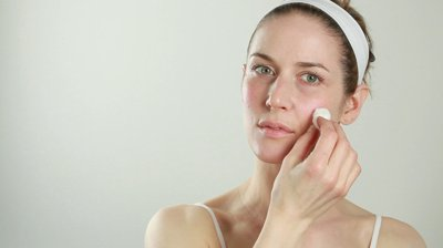 Image of woman using a cotton ball on her face.