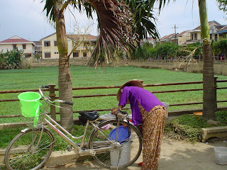 Woman with her bike and Vietnamese hat