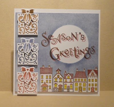 Christmas card, houses with a moon above, Season's Greetings sentiment and 3 presents on the left