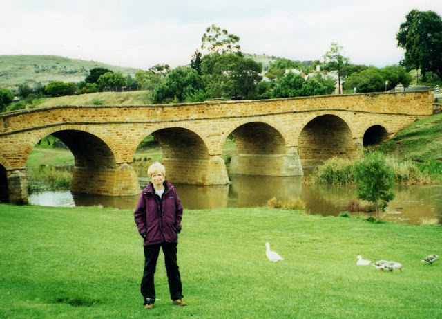 woman in rain pants and jacket in front of a historic bridge near Richmond, Tasmania