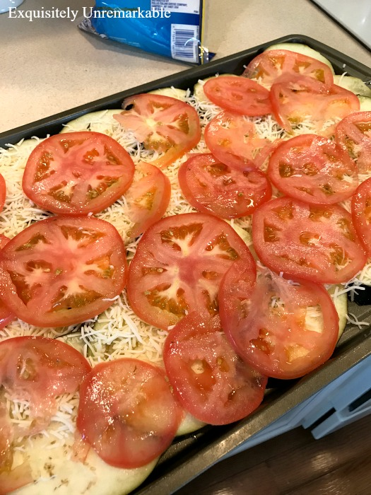 Eggplant Pizziola with tomatoes and shredded cheese on a metal cooking tray