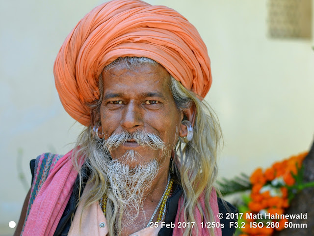 matt hahnewald photography; facing the world; gorakh nath; monk; monastery; bhavnath; bhavnath fair; character; face; earrings; ears; holed; eyes; facial expression; eye contact; full beard; turban; orange; consent; empathy; rapport; respect; traveling; religious; traditional; cultural; hinduism; festival; event; mela; devotee; pilgrim; junagadh; gujarat; asian; indian; western india; one person; male; middle-aged; man; picture; photo; face perception; physiognomy; educational; nikon d3100; nikkor af-s 50mm f/1.8g; prime lens; 50mm lens; 4x3 aspect ratio; horizontal orientation; street; portrait; closeup; headshot; seven-eighths view; outdoors; color; posing; authentic; smiling; kanphata; yogi; darshani; gorakhnathi; shaivism; long hair; smiling eyes; splitted ears