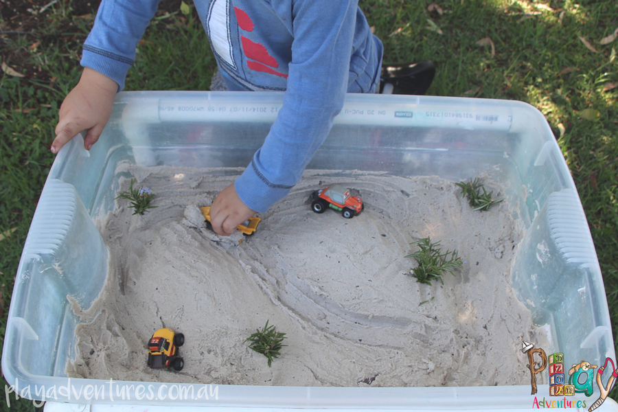 Driving toy cars through the sand dune small world play