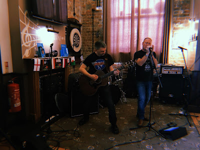 two men singing and playing guitar in a pub