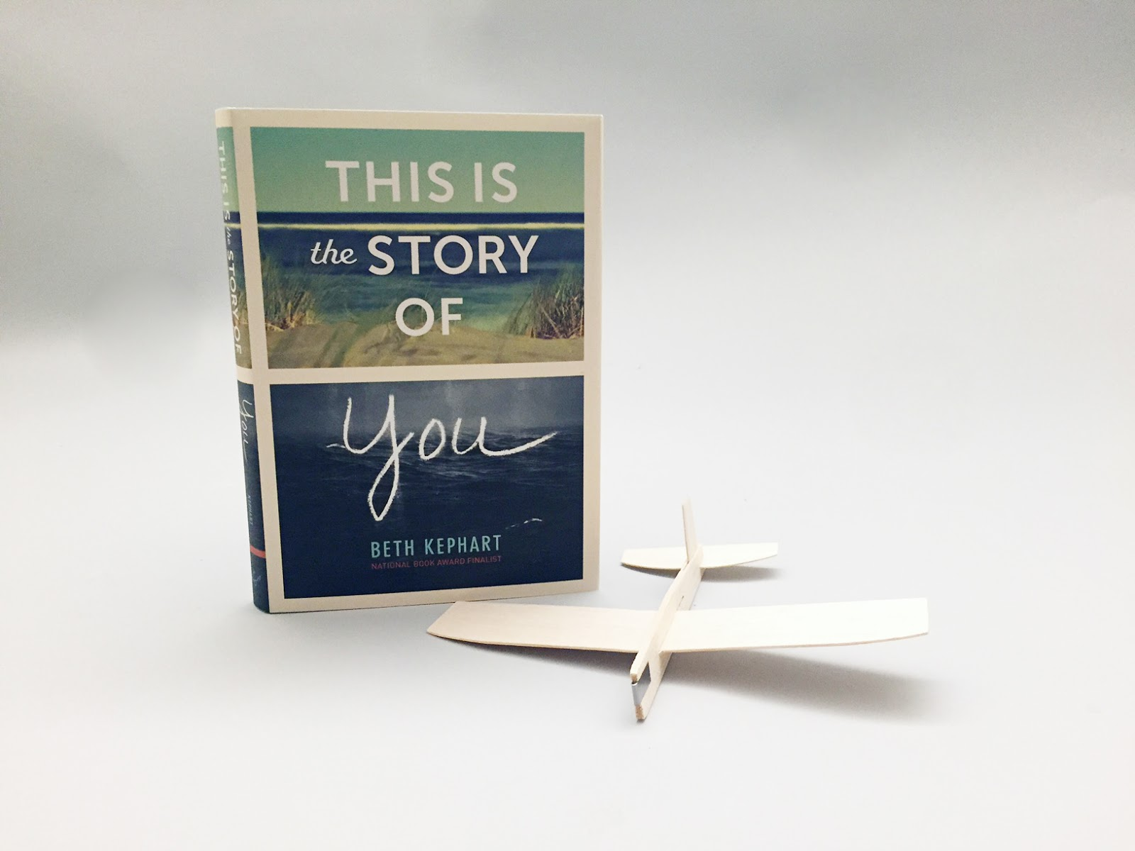 There is ocean storm community friendship family mystery in this is the story of you there are model airplanes pinned to a ceiling and bobbing in the