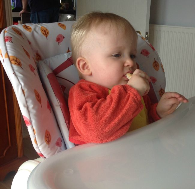 Baby in high chair eating hand held food