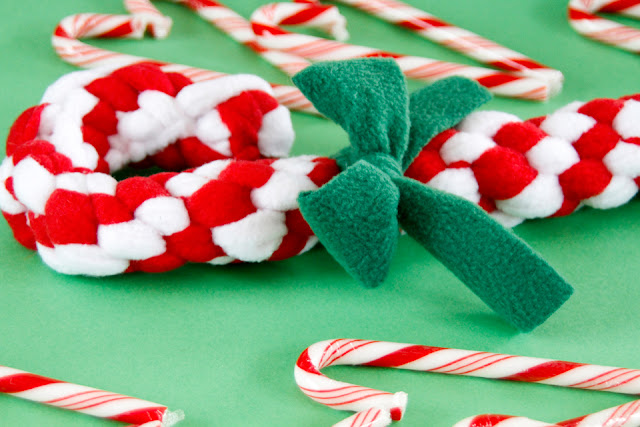 Homemade candy cane shaped dog tug toy (red and white, green bow)