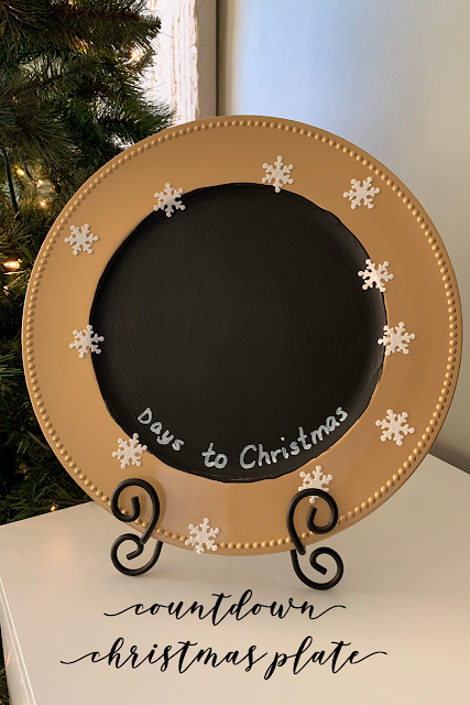 Round gold plate charger with black chalkboard paint in the center, with the words Days to Christmas written in white sharpie paint on the bottom and decorated with white snowflakes.