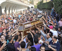 Mourners carry the coffins of victims of clashes between protesters and security forces in Cairo, Egypt, Monday.