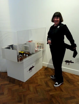 Woman in a gallery, holding  a glass of wine next to an exhibit and showing the tails on her coat.