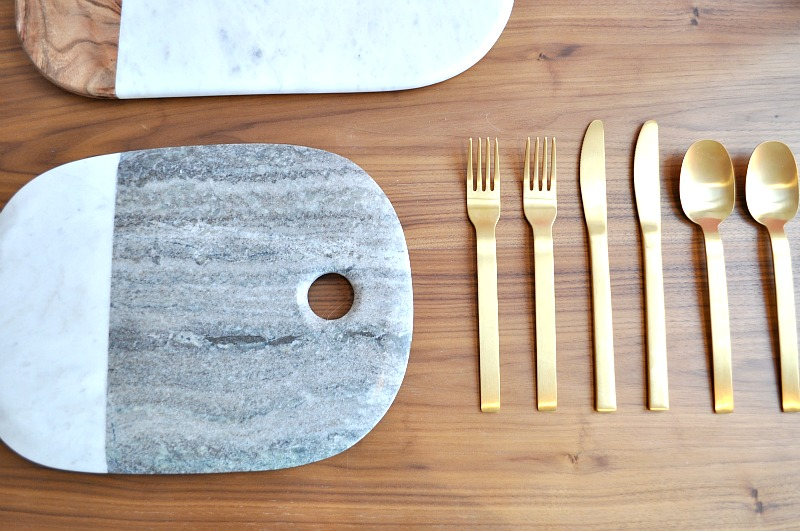 Grey marble chopping boards and gold cutlery
