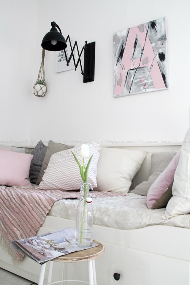 Daybed mit weißen beigen rosafarbenen Kissen, einem Hocker mit Tulpe in einer Flasche und darüber hängt eine schwarze Scherenlampe sowie ein DIY Typo Letters Acrylbild
