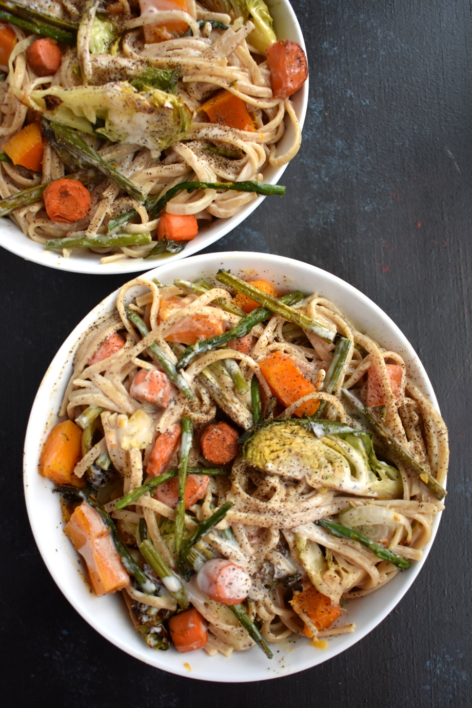 Roasted Vegetable Fettuccine Alfredo is loaded with a garlicky, cheesy creamy sauce with whole-wheat noodles, roasted butternut squash, Brussels sprouts, carrots, onions and asparagus! www.nutritionistreviews.com