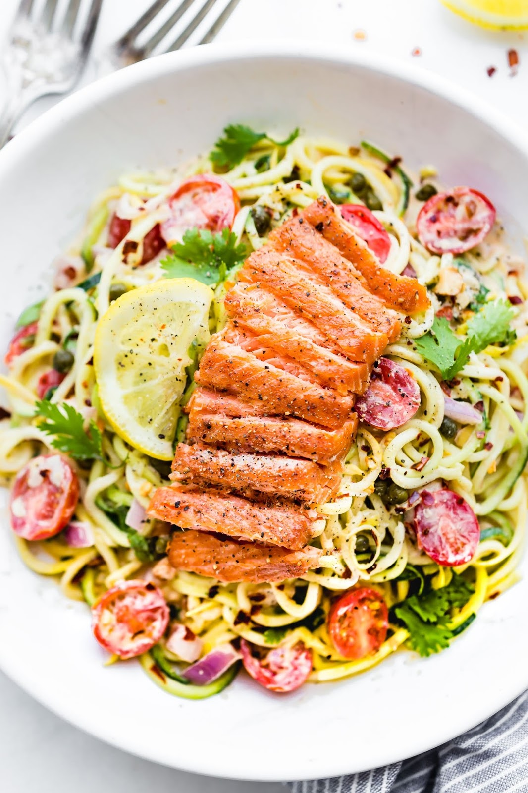 Cajun Smoked Salmon Zucchini Noodles Salad  A zippy cajun sauce tossed in chopped vegetables and zucchini noodles then topped with peppery smoked salmon. Healthy Swaps - Zucchini noodles and Smoked salmon instead of pasta or chicken.