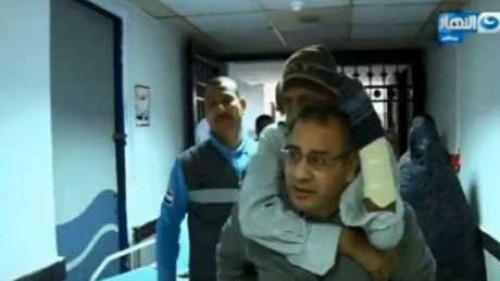 جابر القرموطي يحمل مريضًا على ظهره إلى معهد الكلى.. ومسؤولة تواجهه