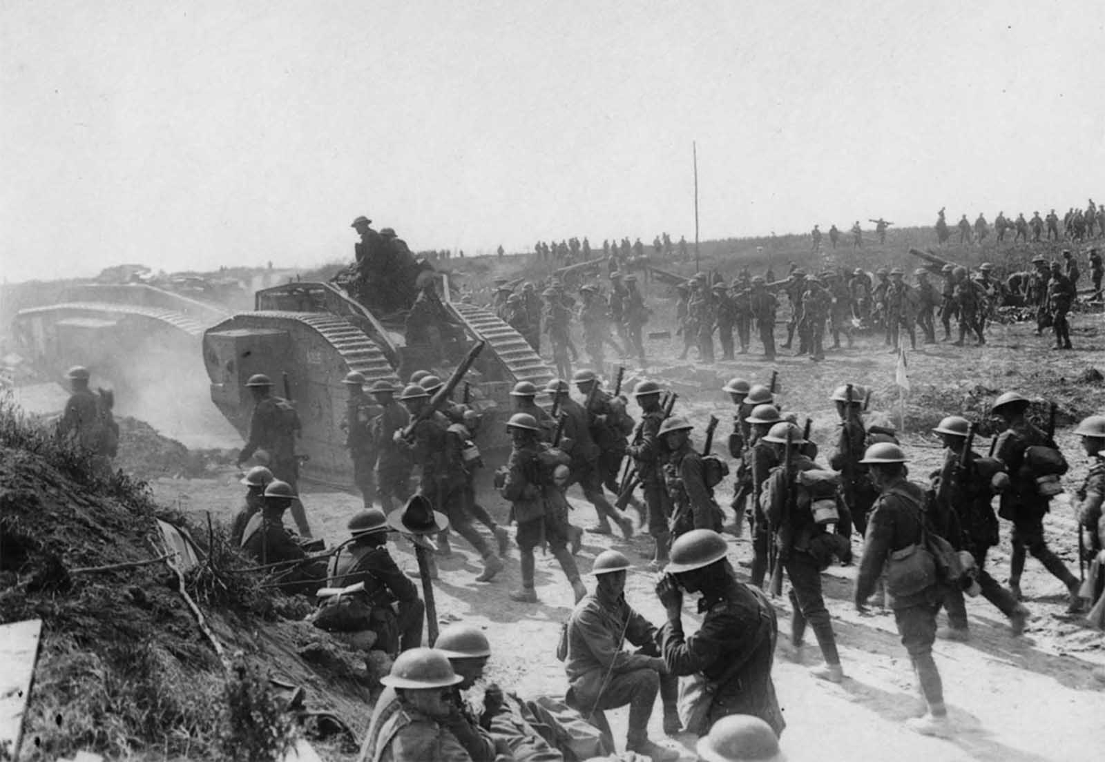 Allied advance on Bapaume, France, ca. 1917. Two tanks are moving towards the left, followed by troops. In the foreground some soldiers are sitting and standing at the roadside. One of them appears to be having a drink. Beside the men is what appears to be a rough wooden cross with an Australian or New Zealand service hat on it. In the background other troops are advancing, moving field guns and mortars.