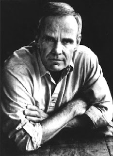Fotografía de Cormac McCarthy en blanco y negro de brazos cruzados mirando a la cámara