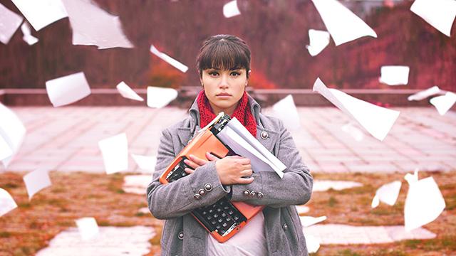 Photo d'une femme qui tient une machine à écrire