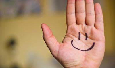 una cara feliz dibujada en la palma de la mano