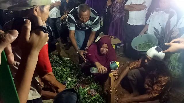 Istri korban penembakan saat meratapi nisan korban di pemakaman.