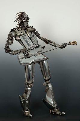 Escultura de hombre tocando la guitarra eléctrica.